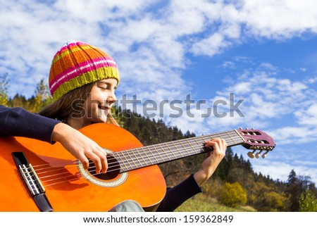 Little girl playing guitar outdoor - stock photo