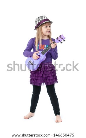 Little girl playing guitar, pretending to be a rock star - stock photo