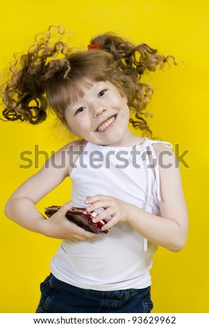Little girl playing handheld portable game console. Yellow background - stock photo
