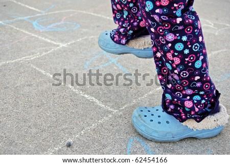little girl playing hopscotch - stock photo