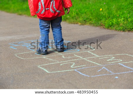 little girl playing hopscotch game after school