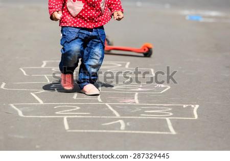 little girl playing hopscotch on asphalt outdoors - stock photo