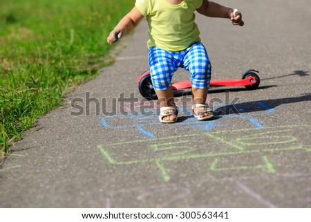 little girl playing hopscotch on playground outdoors - stock photo