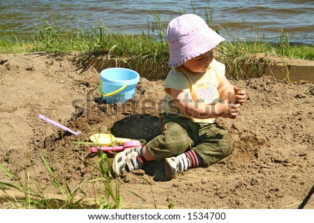 little girl playing in a sandbox on a beach - stock photo