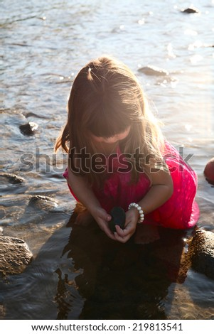 Little girl playing in a shallow stream of water - stock photo