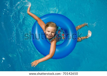 Little girl playing in blue water - space for text - stock photo
