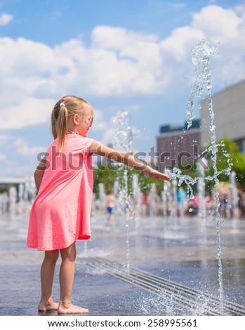 Little girl playing in open street fountain at hot sunny day - stock photo