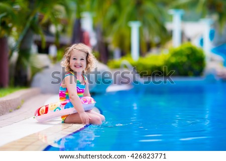 Little girl playing in outdoor swimming pool in tropical resort. Child learning to swim. Toddler kid with inflatable toy ring. Summer beach vacation for family with children. Water fun for kids. - stock photo