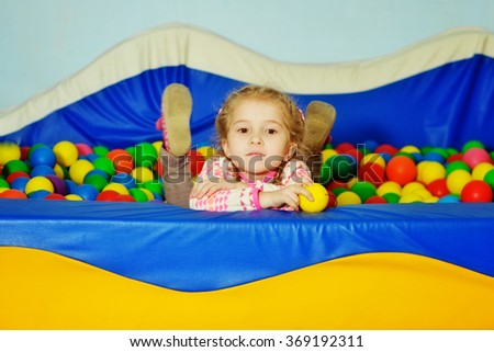 little girl playing in playground colorful ball pool - stock photo