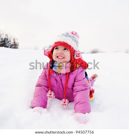 Little girl playing in snow - stock photo