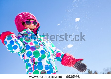 Little girl playing in snowballs in wintertime - stock photo
