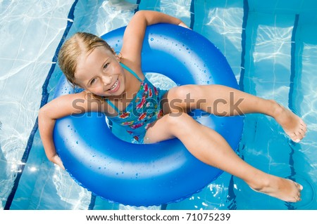 Little girl playing in swimming pool - stock photo