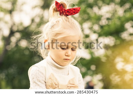 Little girl playing in the dandelion field. White dress with light brown bow. Red ribbon on her head.