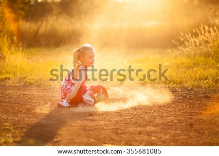 little girl playing in the dust with a stick - stock photo