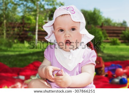 little girl playing in the garden on a sunny day. carefree childhood - stock photo