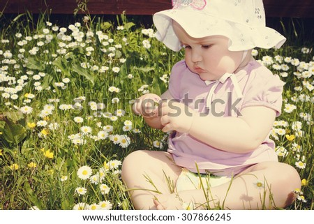 little girl playing in the garden on a sunny day. carefree childhood. image is tinted - stock photo