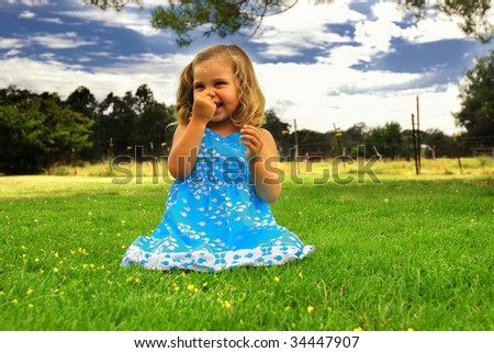 Little girl playing in the grass at a horse farm - stock photo