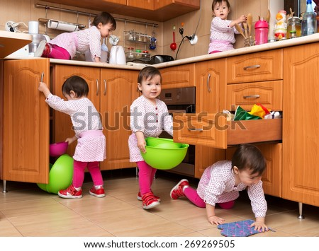 Little girl playing in the kitchen - stock photo