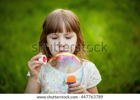 Little girl playing in the park with a bubble - stock photo