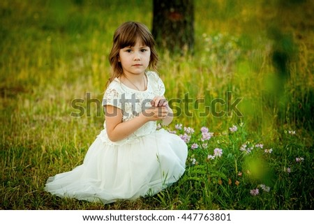 Little girl playing in the park with a toy - stock photo