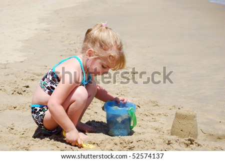 little girl playing in the sand - stock photo