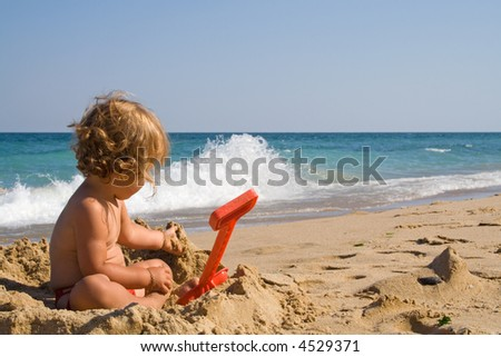Little girl playing in the sand on the summer beach