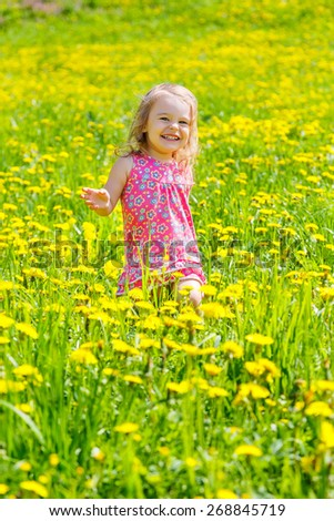 Little girl playing in the spring park - stock photo