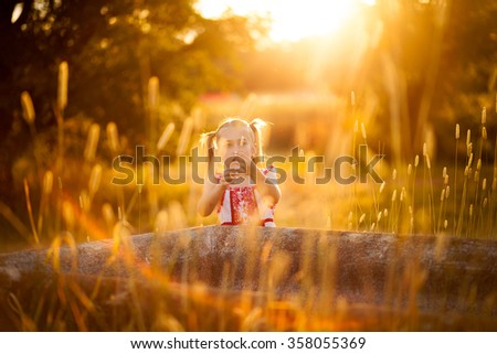 little girl playing in the sun - stock photo