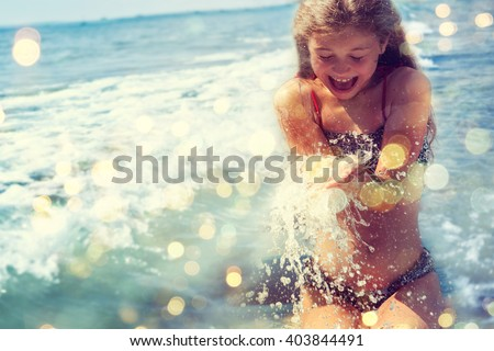 Little girl playing in the waves at sea on a sunny day. - stock photo
