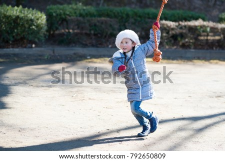 Little girl playing in the winter park