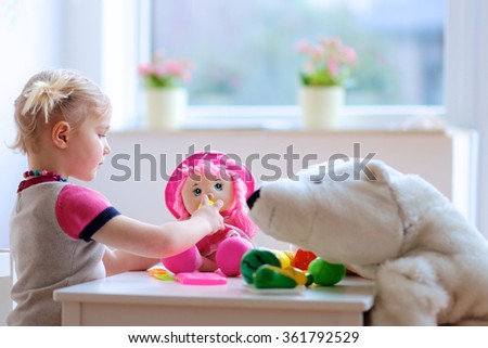 Little girl playing indoors at home or kindergarten. Adorable smiling little child cutting plastic vegetables with knife and feeding her toys, a doll and a teddy bear. Healthy lifestyle for kids. - stock photo