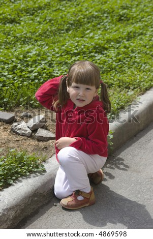 Little girl playing near city lawn with rocks in the middle of the day - stock photo