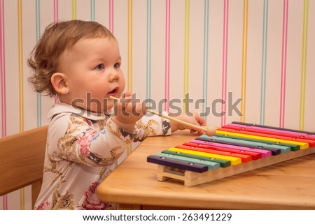 little girl playing on a colorful xylophone