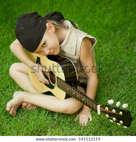 little girl playing on a guitar