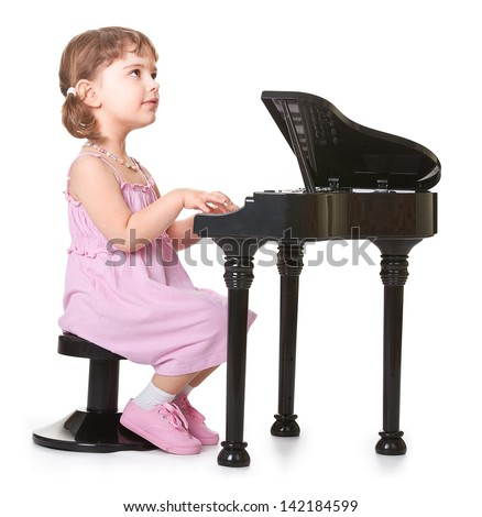 little girl playing on a miniature piano . kid with musical instrument  - stock photo