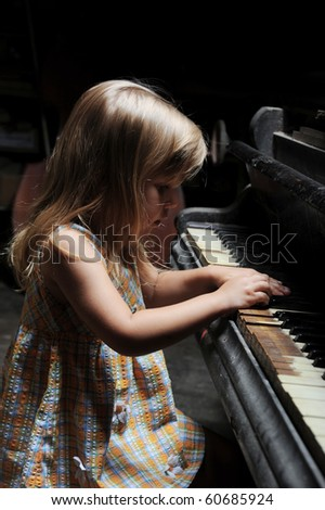 little girl playing on an old black piano