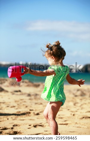 Little girl playing on beach with water can