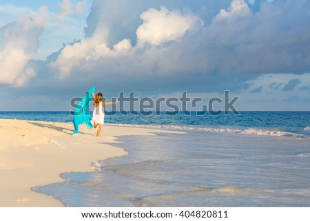 Little girl playing on beautiful ocean beach - stock photo