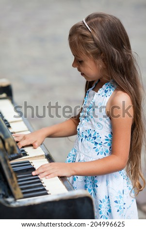 Little girl playing on  old black piano outdoors - stock photo