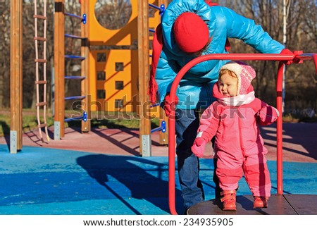 little girl playing on outdoor playground in autumn - stock photo