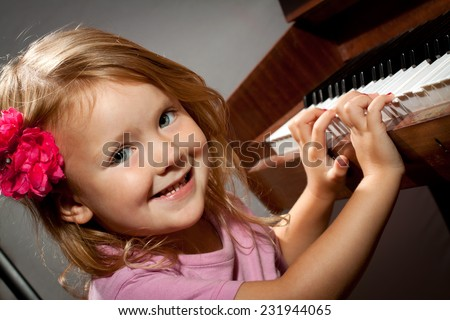 Little girl playing on piano - stock photo