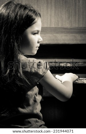 Little girl playing on piano, black and white - stock photo