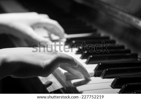 Little girl Playing on piano keyboard. Black and White Image with Selective focus - stock photo