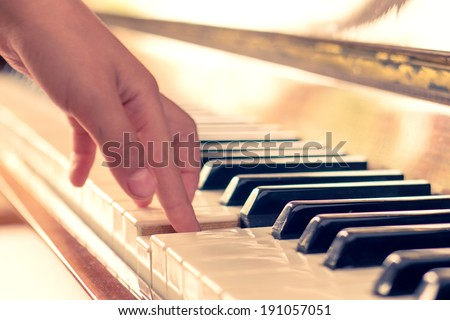 Little girl playing on piano. Warm color toned photo - stock photo