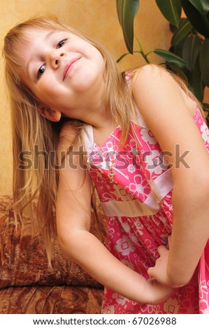 Little girl playing on sofa at her home and imagine she is model. Lifestyle. - stock photo