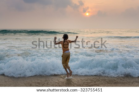 Little girl playing on the beach with strong wave during sunset