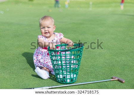 little girl playing on the lawn of golf balls and a stick - stock photo