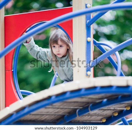 Little girl playing on the playground at spring day