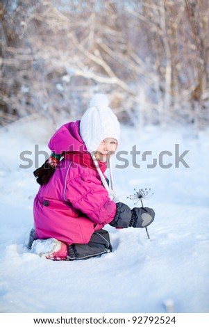 Little girl playing outdoors on beautiful winter day
