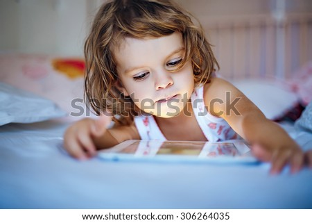 little girl playing tablet. - stock photo